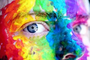 hombre que mira de cerca con la cara pintada con los colores LGBTI